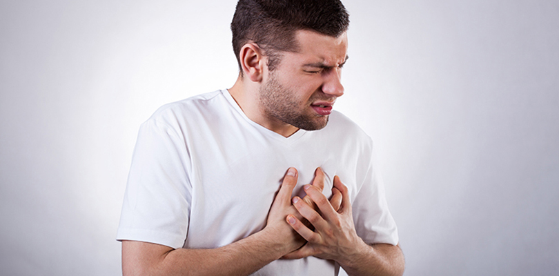 Man clenches his chest due to chest pain