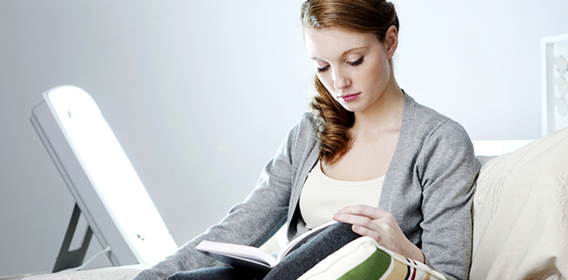 Woman is reading a book while receiving light therapy