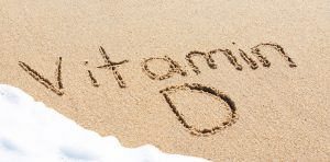 "The words ""Vitamin D"" is written in sand"