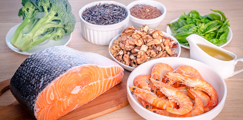A table is set out with salmon, shrimp, broccoli, nuts and seeds