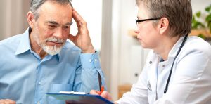 Older gentleman sits with doctor explaining symptoms to him