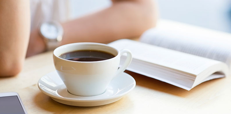 Woman sitting with a cup of coffee and book