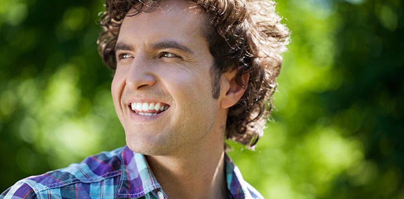 A man is smiling while enjoying nature