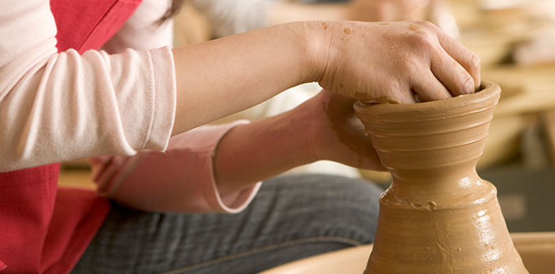 An individual is at a pottery studio make a vase