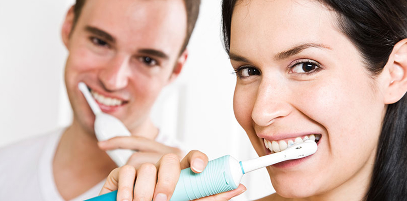 A couple are brushing their teeth