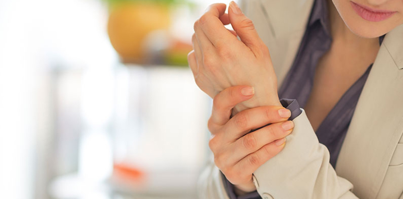 Woman is holding her wrist