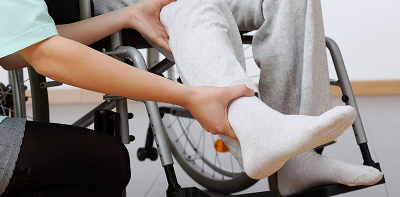 Patient sitting in wheelchair as the doctor assess foot.