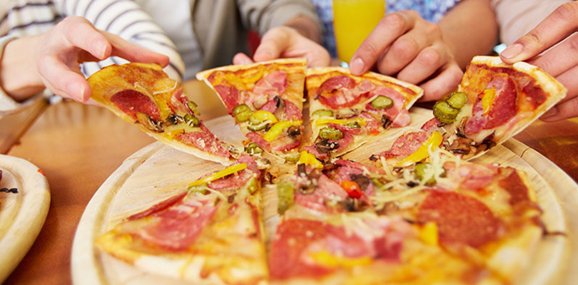 A group of people enjoying a slice of pizza