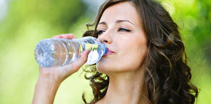 Woman is drinking bottled water