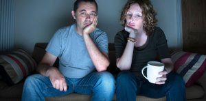A couple is sitting on a couch watching TV looking tired