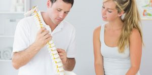 Woman is listening to her chiropractor explain good posture