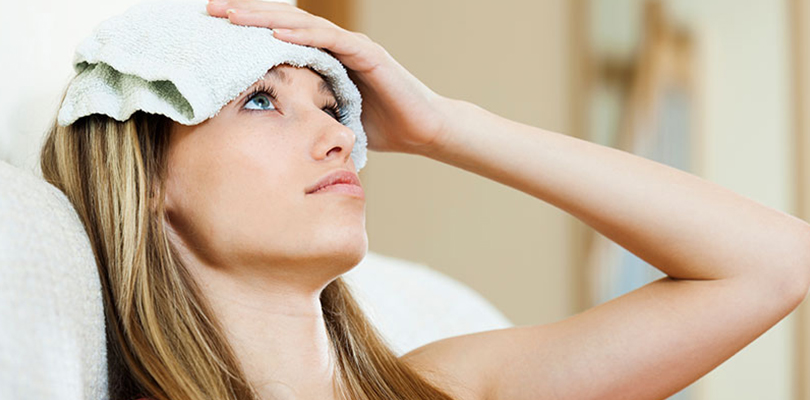 Woman is holding a wet cloth on her forehead