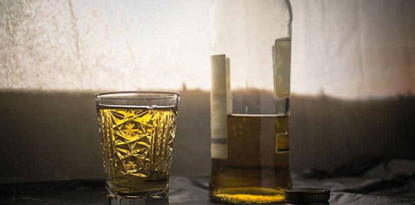 A glass full of alcohol sits beside a half-drunken bottle
