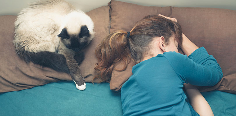 A woman is sleeping while her cat is sitting on a pillow beside her