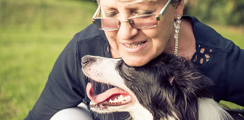 An older woman is nuzzling with her dog