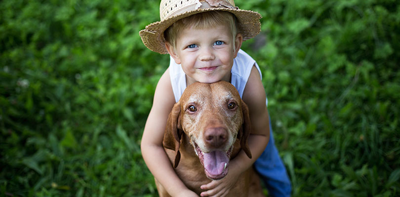 A child is hugging his dog