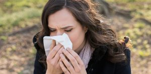 A woman is blowing her nose into a tissue