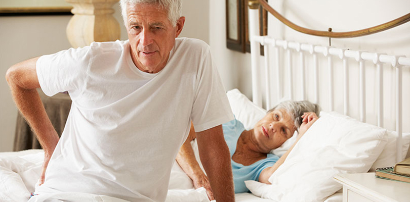 Older gentleman getting out of bed with back pain