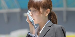 Young woman is holding a cloth to her sweaty face