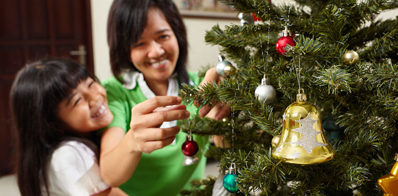 A mother and daughter are hanging ornaments on a tree