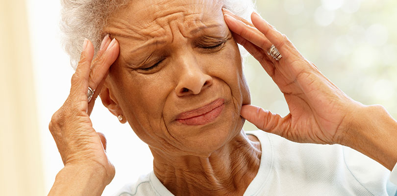 An older woman is experiencing extreme pain in her head