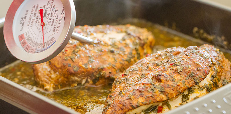 A meat thermometer is measuring the internal heat of a chicken breast