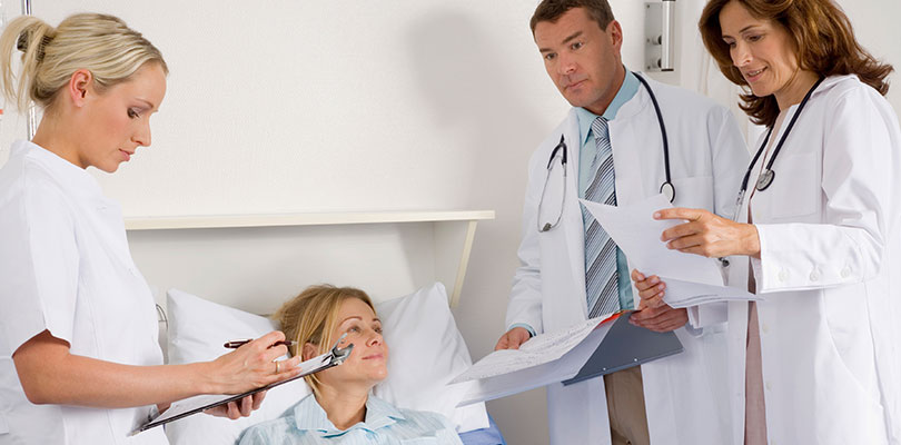 Three doctors surround patient and talk about options