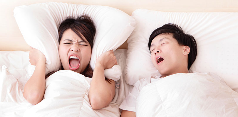 A woman wraps a pillow around her ears to block her husband's snoring