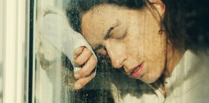 A woman is leaning on window glass looking sad