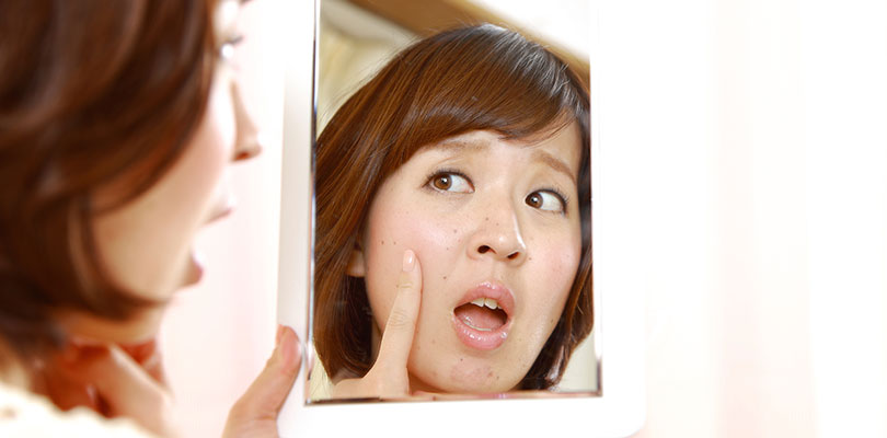 A woman is looking in the mirror and pointing at a mole