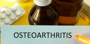 "The word ""Osteoarthritis"" is printed on a sheet of paper with medications in the background"