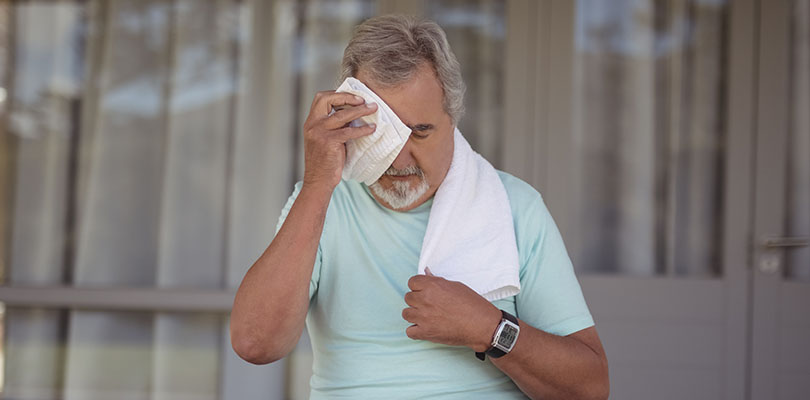 Senior man wiping sweat off his face with towel