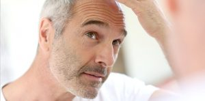 Middle aged man examines his hairline in a mirror