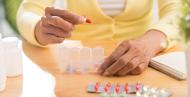 A woman is holding chronic pain management medication in her hand