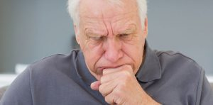 An older gentleman is coughing, one of the many symptoms of pneumonia