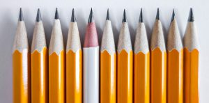 A row of pencils are all the same color and height besides one