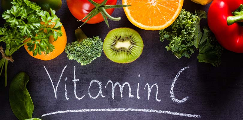 The word vitamin c is written on a blackboard with vitamin c foods above it