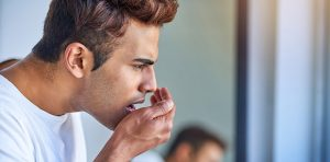 A man is performing a bad breath test on himself