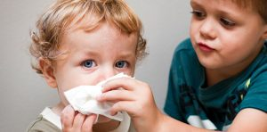 A brother is helping his sibling with a runny nose