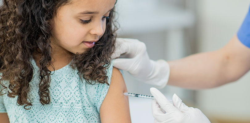 A young girl is receiving a vaccine from a doctor