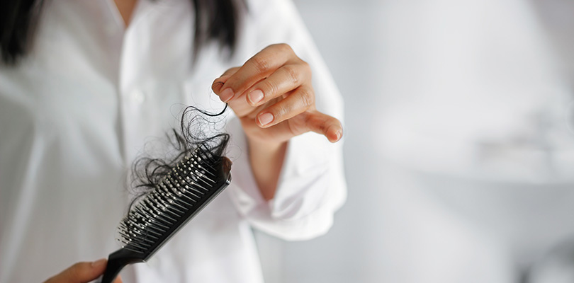 A woman is picking hair out of her comb