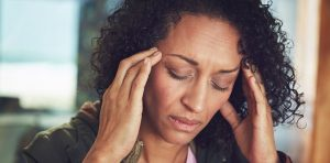 A woman is experiencing a migraine