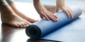 An person is rolling up her yoga mat, a popular yoga equipment for beginners.