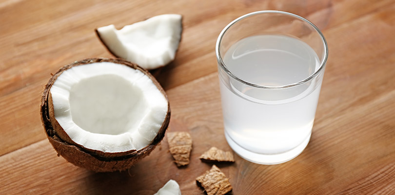 A glass of coconut water is on a table.