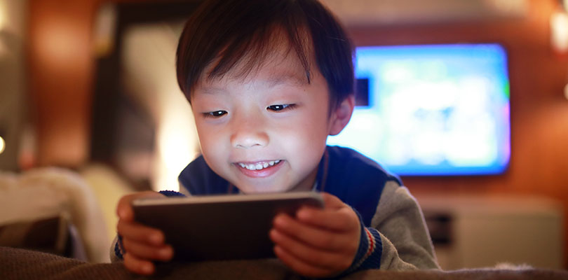 A child is looking at a cellphone screen