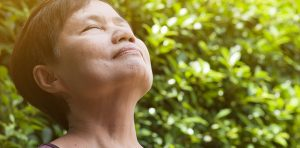 A mature woman is practicing breathing exercises for anxiety