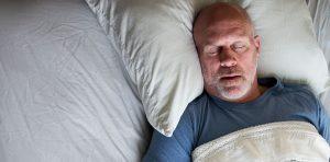 An older gentleman is snoring in bed