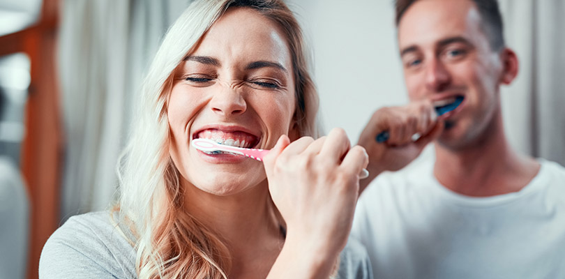 A man and a woman are brushing their teeth