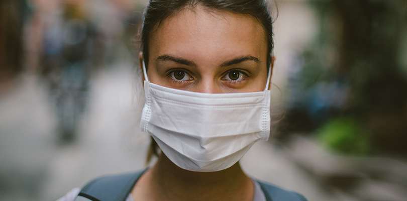 A woman is wearing an allergy mask