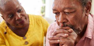 Woman comforting older man